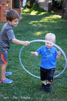 A simple way to include toddlers in gross motor activities with hula hoops is by holding up a hoop for them to walk through.