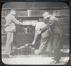 Three men dusting books at the New York Public Library, 1913.
