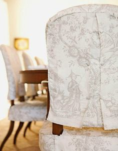 Two-piece tailored slipcovers made of cotton toile in cream and taupe are embellished with covred buttons. - Traditional Home ® / Photo: Karyn Millet