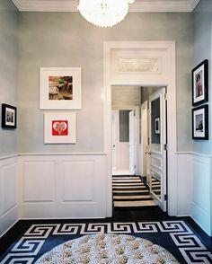 A round tufted ottoman paired with a Greek-key rug in an entryway