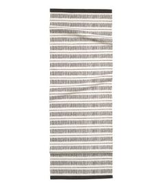 Rectangular rug in woven cotton fabric with a printed pattern at front.