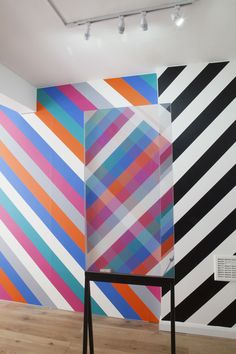 Norwegian designer Kim Thome has installed a series of two-way mirrors that reflect vinyl stripes covering the walls of a London gallery