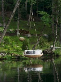 Garden swing over a pond of water.