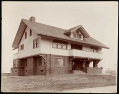 Photograph of an unidentified Craftsman-style house in Los Angeles, [s.d.]. The two-story house is at center and is facing slightly to the right. The first floor is made of brick, while the second floor is light stucco. A covered porch and large balcony can be seen at right, while a dormer protrudes from the roof at center. A small brick chimney can be seen at left. The area around the house is not landscaped and is covered with bare dirt.