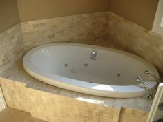 Natural travertine bath surrounds, installed by Mario