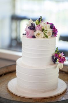 A classical white two-tier wedding cake comes to life with clusters of colour, featuring David Austen roses, lavender and freesia. www.jademcintoshflowers.com.au www.projectcake.com.au