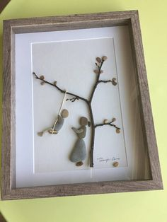 Beautiful pebble picture with swing motif using a mixture of natural materials. Portraying the love and excitement of childhood, this 11x14 grey shadow box as shown may be the perfect unique gift or a beautiful asset to any room that will even remind the adult back to their