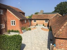 Courtyard constructed in Chiddingfold using animal feed troughs and old water tank to create beds