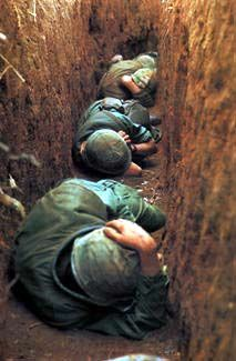 ROBERT ELLISON Khe Sanh, Vietnam, 1968     U.S. Marines huddle as North Vietnamese shell the airfield, aiming for incoming supply aircraft.  (Black Star)