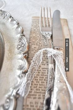 Silverware wrapped in a napkin and then a wrap of old book/music and Lace