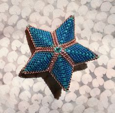 Little star made with delicas in two blue shades and one gold.  From http://www.amazon.com/Shaped-Beadwork-Beyond-Dimensional-Inspirations/dp/145470361X/ref=sr_1_1?s=books&ie=UTF8&qid=1398808595&sr=1-1&keywords=diane+fitzgerald  Now I am going to relax with a bracelet before I tackle an icosahedron.  All this peyote is a bit mind numbing.  But these little projects are a great way to give beady gifts to the men in my life.  Particularly the math and physics oriented ones.