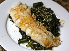 """From article: """"Cod and kale may seem like an unlikely combination, but, when cooked until tender, the robust green actually makes a fantastic backdrop to the delicate, white-fleshed fish. In this quick and easy one-skillet dinner, we braise dinosaur kale (also known as Tuscan kale) in an aromatic mixture of rice wine, sesame oil, garlic, and ginger, then steam fillets of codfish on top."""""""