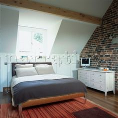 bedroom attic conversion with exposed brick wall and timber beam