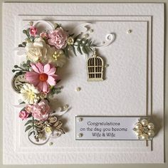 Measuring approx. 7.75 inches square, this stunning gay wedding card congratulating Wife & Wifeoozes cottage chic charm combined with a minimalist look. White hammered effect card stock has been layered with foam pads to add dimension. Die cut swirls and foliage with a mixed floral corsage together with wooden lazer cut birdcage, pocket watch and bow and faux pearls and diamantes all come together to create this keepsake of a very special day  Card personalisation:  This card can be pers...