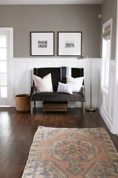 Vintage rug adds warmth and color to this neutral entryway. An upholstered settee adds functionality. Board and batten make it charming.