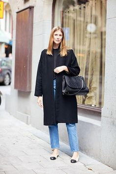 A black coat paired with straight-cut denim and cap toe flats is a classic combo for looking chic in the cold.