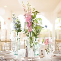 Simple wildflower arrangements in pinks and purples filled decorative glass bottles   Melissa Robotti Photography   Broadway Florist Of Newport