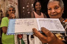 """Cuba food ration stores 'celebrate' their 50th anniversary.  A woman shows a """"libreta,"""" or ration card in Santiago de Cuba on July 10, 2013 - 50 years being slaves of the commie government that will tell them what and how much they can buy."""