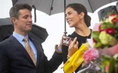 Liefde is… het lekwater van de paraplu opvangen om je vrouw droog te houden. En als vrouw weten dat de liefde van je man deels ook door de maag gaat. Dat pakje chocoladebiscuitjes ging dus mooi mee de auto in © Lukas Coch / Getty Images
