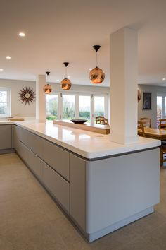 The copper pendant lights add warmth to the bright Glacier White Corian worktops of this kitchen from Planet Furniture Best Modern Kitchen Lighting Ideas and Tips kitchen furniture Small Kitchen Lighting Ideas Pictures for Low Ceilings Open Plan Kitchen Dining Living, Open Plan Kitchen Diner, Grey Kitchen Diner, Grey Gloss Kitchen, Kitchen Family Rooms, Living Room Kitchen, Modern Kitchen Design, Interior Design Kitchen, Small Kitchen Lighting