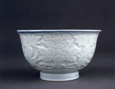 Porcelain bowl. Underglaze blue on the inside with a crane perched on a rock under a pine tree in double circle. Carved scrolling peonies and leaves on the outside. Inscription on base. (Ming dynasty)