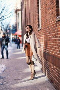 Neutral Mix: Taupe overcoat on Camel leather skirt with wide belt at waist, and calf-height suede boots. Professional street style.
