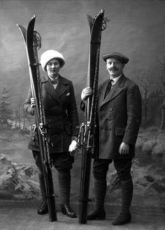 1913 - Gruppeportrett, mann og kvinne i skiutstyr i studio. Begge i bukse/nikkers.