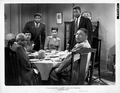 Publicity still of Sidney Poitier (standing right) and others in 'No Way Out' (20th Century Fox), with Ossie Davis, Ruby Dee, Mildred Joanne Smith (seated, center) Frederick O'Neal, and Maude Simmons, 1950.