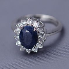 """Genuine Sapphire Royal Engagement Ring""   This beautiful 3 carat genuine sapphire ring looks just like the Royal engagement ring. The oval-shaped center stone is surrounded by 14 diamond-like sparkling cubic zirconia. This ring is an absolute must have!"