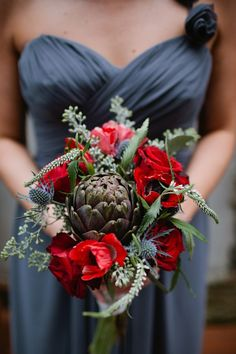 A stunning, dark toned wedding bouquet featuring roses, poppies and artichokes.