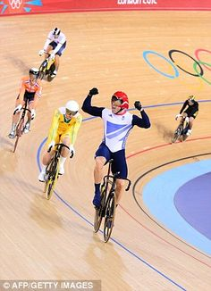 Sir Chris Hoy holds his arms aloft after clinching victory