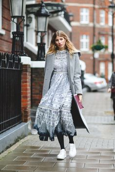 That peasant dress hiding in the back of your closet? Give it new life with tights, sneakers, and a gray overcoat. #refinery29 http://www.refinery29.com/2016/02/103453/london-fashion-week-fall-winter-2016-street-style-pictures#slide-67