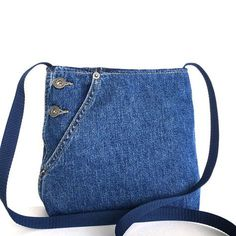 If you are heading out for a walk or shopping at the nearby store,this mini cross body bag is a perfect addition to your outfit. It is made from recycled denim pant,and has 2 pockets. One patch pocket with flap and button closure and one open pocket. Original metal buttons on the one side give an asymmetrical look to the bag. A magnetic snap fastens opening of the bag. Strap is made from dark blue webbing. It is lined with light grey fabric. Measurements: opening width:7.5 base width:9…