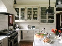 Gone are the days when a kitchen range hood stood out like a sore thumb. Designer Rebekah Zaveloff incorporated it into the design by covering the custom-made range hood with the same porcelain subway tile as the walls, causing it to virtually disappear, allowing the kitchen's architectural elements to take center stage.