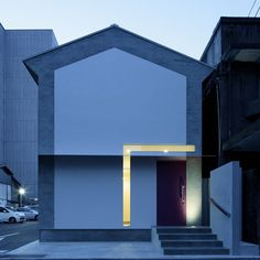 The L-shaped glazing that punctures the facade of this house creates an illuminated frame around the entrance.