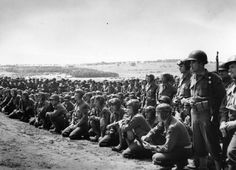 June 6, 1944. American soldiers line up for a briefing prior to receiving their D-Day assignments.