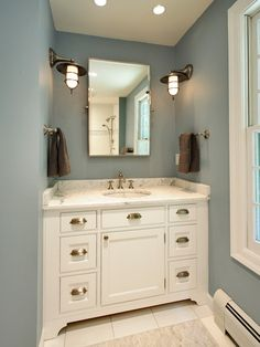 Olga Adler Interiors Fantastic blue bathroom design with blue walls paint color, white bathroom cabinet vanity with brushed nickel pulls, marble counter top, rectangular pivot mirror, chocolate brown towels and brushed nickel marine sconces. Rustic Wall Sconces, Bathroom Sconces, White Bathroom, Bathroom Lighting, Bathroom Wall, Master Bathroom, Master Baths, Serene Bathroom, Garage Bathroom