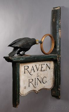 "Carved and Painted ""RAVEN & RING"" Tavern Sign, 20th century, fully carved raven and ring motifs, with incised lettering on the shaped double-sided sign, old paint and gilding, on a wood post mount, (losses, age crack to wing), ht. 47 1/2, wd. 32 1/2 in. Estimate $4,000-6,000(8300)"
