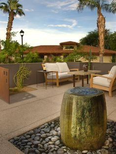 This patio features a stone fountain that flows into a pebble-rock bed, and a small seating area, perfect for a chat or a nice meal.