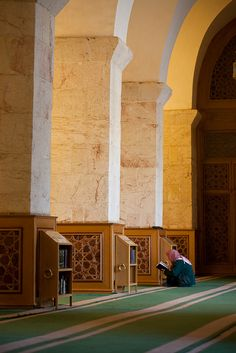 A man quietly reads inside the Great Mosque of Aleppo, Syria