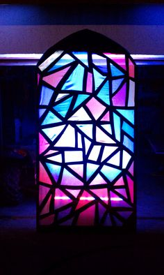 Todd Reed brings us this liturgical stage design incorporating home-made stained glass windows. Todd started out with pink insulation foam from Home Depot and drew a pattern resembling an abstract stained glass window. He created 5 windows (2 - 8', 2-12', 1 - 16') and used an exacto blade to cut out each shape. After cutting out all 525 pieces he used gloss black paint to paint in all the frames and the front of the window. After letting them all dry, he hot glued crushed white voille…