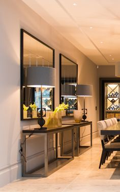 Over-sized double console table and mirror arrangement give elegance and glamour to a contemporary dining space.