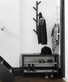 Pequeno hall de entrada com um cabide com a forma de uma árvore e um banco com arrumação para sapatos, ambos em preto