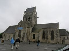 Church at St. Mary Eglese where American parachuters landed - a parachute is draped on top of the church to indicate where one paratrooper landed.