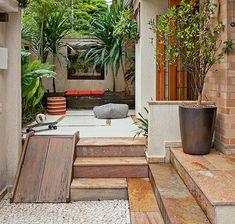A entrada era inútil antes do projeto da Cali Paisagismo. Os moradores queriam uma extensão do living, mas também plantas. Para unir os dois desejos, foi colocado piso de cimento queimado com detalhe de ladrilho hidráulico e, ao redor, um canteiro
