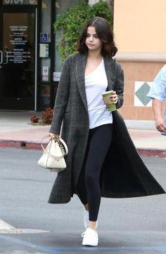 Selena Gomez wearing a gray plaid longline coat, white t-shirt, black leggings, white sneakers, and a cream colored handbag