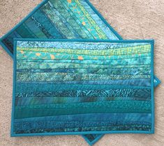 Dont you just love this color of teal? The color of the ocean. Warm water. A bright sunny day on the shore. I made these placemats by piecing and quilting thin strips of cotton fabric that I sew through the polyester batting onto the back. I then hand finish the bindings. At 13x19 inches I