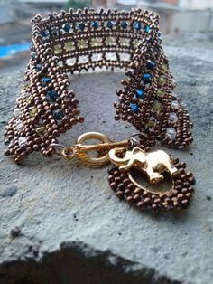 Pulseira toda em cristais swarovski e miçangas feita à mão com acabamento dourado e pingente de elefante.