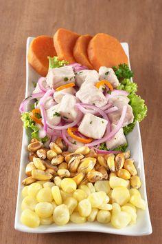 Ceviche, pescado cocinado con limón, sal y otros condimentos. Se acompaña con camote, cebolla, choclo y cancha serrana.