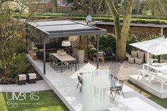 Terras idee: vrijstaand design lamellendak in tuin, creëert extra ruimte om buiten te genieten bij zon en regen. Afwerking met houten lamellen in zijwand tegen wind.